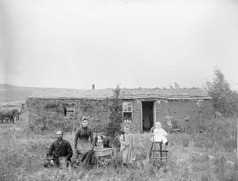 Unbekannte Siedler vor improvisiertem Haus