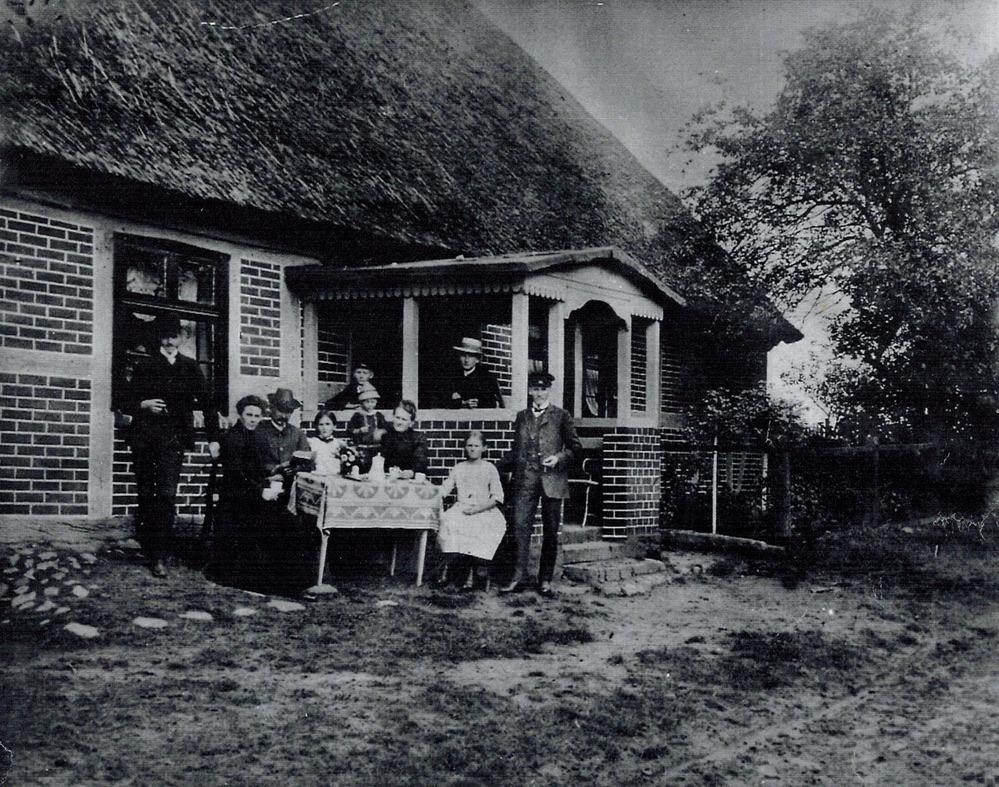 Foto von der bäuerlichen Familie vor dem schilfgedeckten Haus, um 1910