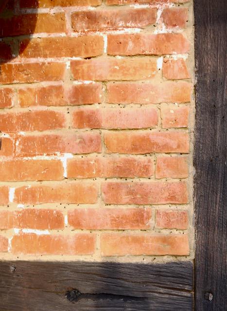 Ein wettergeschütztes Fach mit Resten der Bemalung über ursptünglicher lehmgemauerter Ziegelsetzung in der Insekten brüten, Wohn-Stall-Haus eines Erbpachtbauern von 1832 in Stuer/ Mecklenburg